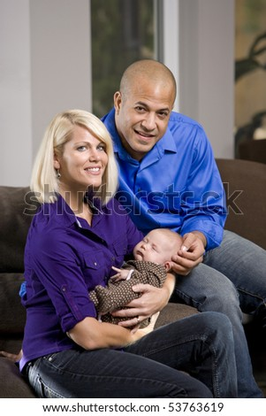 Happy parents cradling sleeping 3 month old baby at home