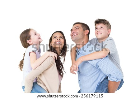 Happy parents giving piggyback ride to children while looking up over white background - stock photo