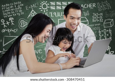 Happy parents helping their child studying with laptop and fun - stock photo