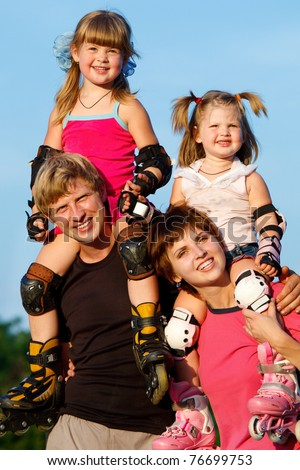 Happy parents holding children in roller skates - stock photo