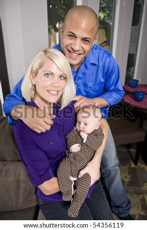 Happy parents holding 3 month old baby sitting on sofa at home
