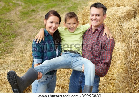 Happy parents holding their cute son in countryside