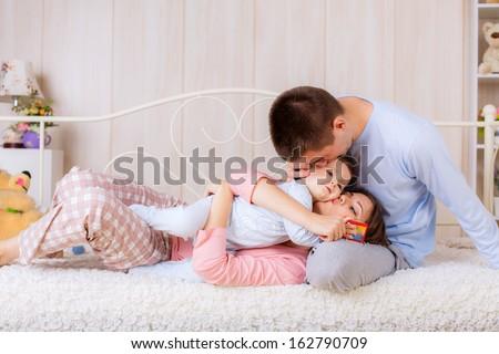 Happy parents kissing baby - stock photo