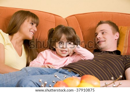Happy parents looking at each other with their daughter between them and talking - stock photo