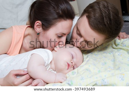 Happy parents near a sleeping baby