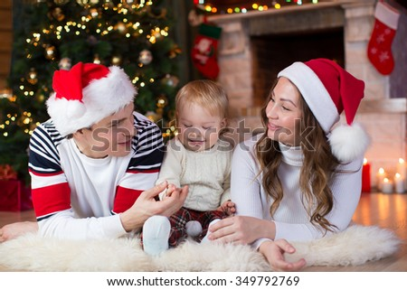 Happy parents playing with kid son lying near Christmas tree and fireplace  in living room