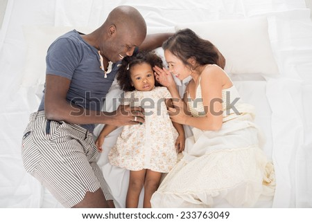 Happy parents playing with their daughter, view from above - stock photo