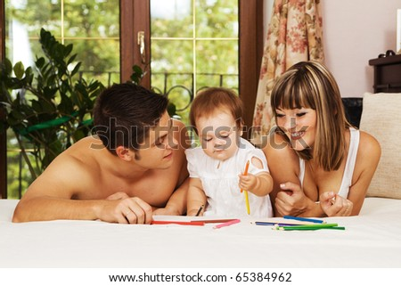 Happy parents playing with their little daughter at bedroom - stock photo