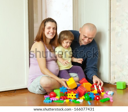 Happy parents plays with child in home interior - stock photo