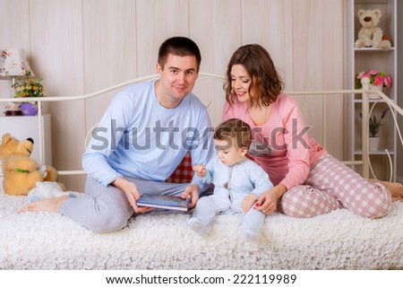 happy parents read a book your child in the nursery. all dressed in pajamas - stock photo