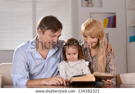 happy parents reading a book their daughter at home - stock photo