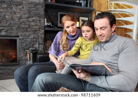 happy parents reading their young daughter a story - stock photo