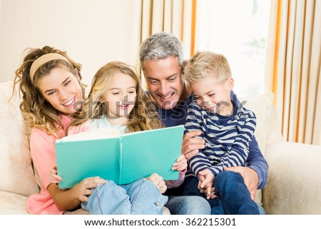 Happy parents reading to their kids on the couch - stock photo