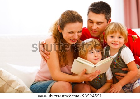 Happy parents reading to twins daughters