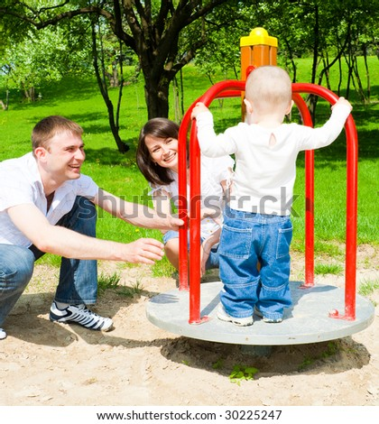 Happy parents rotating platform with their son - stock photo