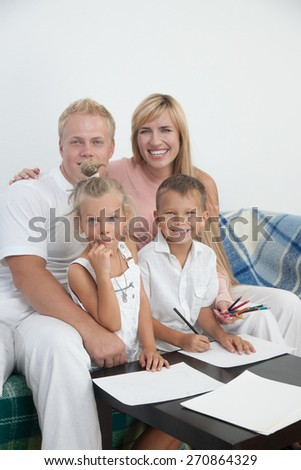 Happy parents sit and draw with kids on paper - stock photo