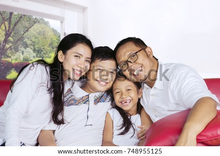 Happy parents sitting on the couch with their children while laughing together in the living room