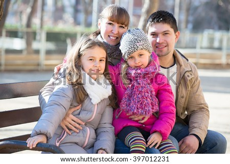 Happy parents sitting with little daughters on bench outside. Focus on girls