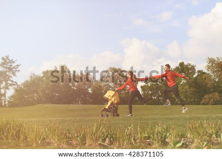 Happy parents spending their sport time in park. People running and forgetting about children. Taking care of children. - stock photo