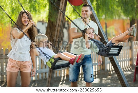 Happy parents swinging children at park. Focus on woman - stock photo