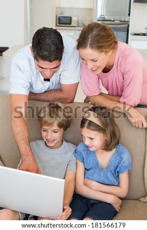 Happy parents teaching children to use laptop in sitting room