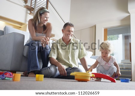 Happy parents watching daughter playing with toy