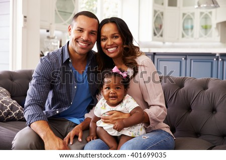 Happy parents with a baby girl sitting on mumâ??s knee - stock photo