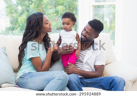 Happy parents with baby girl on couch at home in the living room - stock photo