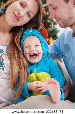 Happy parents with baby son dressed in little monster costume at Christmas time - stock photo