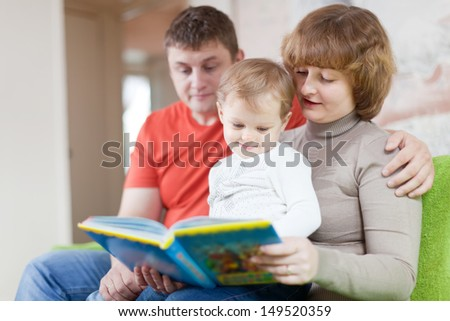 Happy parents with child looks the book in home interior - stock photo