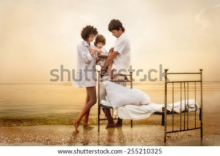 Happy parents with child on sea beach at sunset - stock photo