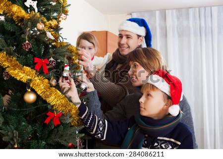 Happy parents with children decorating Christmas tree at home