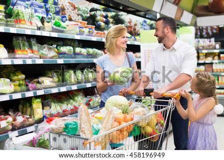 Happy parents with daughter choosing lettuce in hypermarket