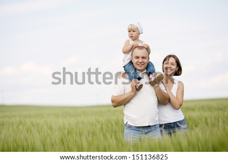 happy parents with daughter in the field