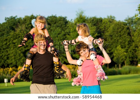 Happy parents with kids in roller skates - stock photo