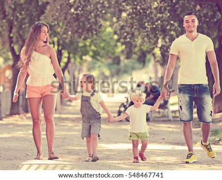 Happy parents with little children in park on summer day