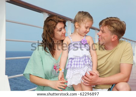Happy parents with small daughter enjoy sea on yacht - stock photo