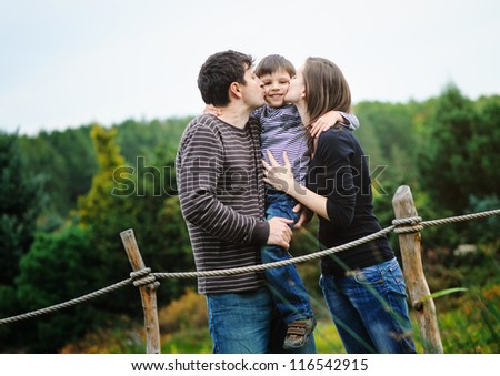 Happy parents with son in a park - stock photo