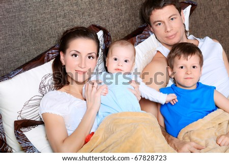 Happy parents with their children in a bed under cover.