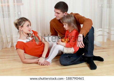 Happy parents with their daughter at home. - stock photo