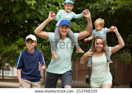 Happy parents with three children walking outdoor and smiling - stock photo