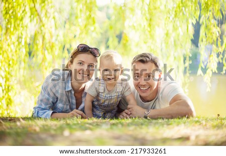 Happy parents with toddler boy. Mother, father and son relaxing on the lawn.