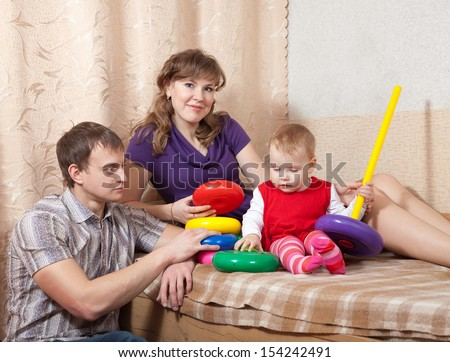 Happy parents with toddler in home interior