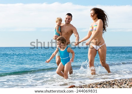Happy parents with two children at sea - stock photo