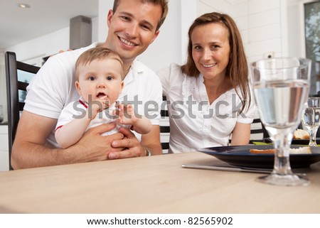 Happy parents with young boy child looking at the camera