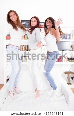 happy party girls jumping on couch at home - stock photo