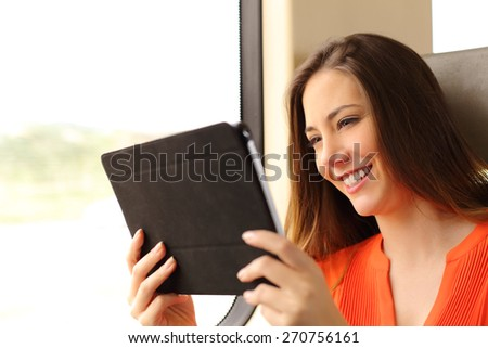 Happy passenger woman reading a tablet or ebook traveling inside a train - stock photo