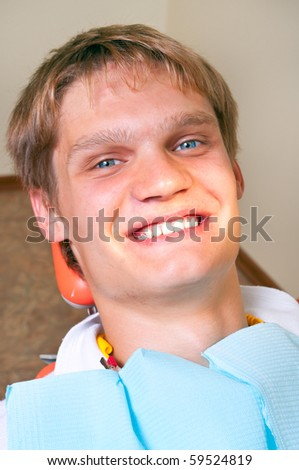 Happy patient in dental chair - stock photo