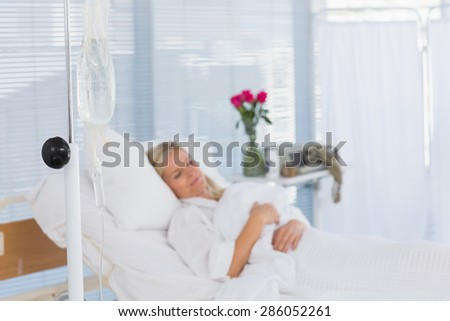 Happy patient lying on her bed in hospital - stock photo