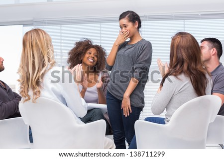 Happy patient standing and feeling overwhelmed while other patients are clapping - stock photo
